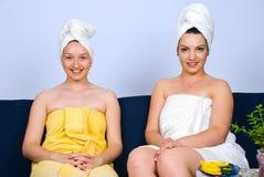 Glückliche Frau zwei auf Couch am Badekurort Stockbild