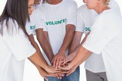 Glückliche Freiwillige, die Hände zusammenfügen Stockfotos