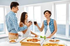 Glückliche Freunde, die Abendessen-Haus haben Essen des Lebensmittels, Freundschaft Stockbild