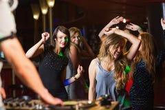Glückliche Freunde, die durch den DJ-Stand tanzen Stockfoto
