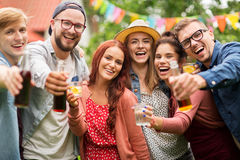 Glückliche Freunde mit Getränken am Sommergartenfest Stockbilder