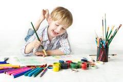 Glückliche freundliche Kindzeichnung mit Pinsel im Album Stockfotografie