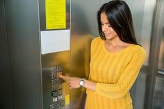 Glückliche Geschäftsfrau, die Aufzugsknopf betätigt Stockfotografie