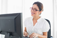 Glückliche Geschäftsfrau, die an ihrem Schreibtisch arbeitet Stockfoto