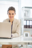 Glückliche Geschäftsfrau, die an Laptop im Büro arbeitet Stockfotos