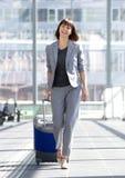 Glückliche Geschäftsfrau, die mit Koffer am Flughafen geht Stockbild