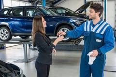 Glückliche Geschäftsfrau Receiving Car Key vom Mechaniker At Garage Stockbilder