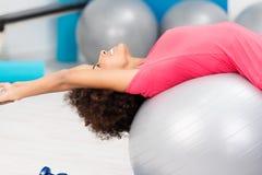 Glückliche geschmeidige Frau, die Pilates in einer Turnhalle übt Stockbild