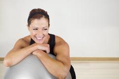 Glückliche gesunde Eignungsfrau, die auf einem Übungsball stillsteht Lizenzfreie Stockfotos