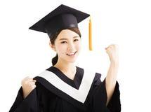 Glückliche graduierende asiatische Studentenerhöhungshand mit Erfolgsgeste Stockfotos
