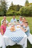 Glückliche Großfamilie, die draußen am Picknicktisch zu Abend isst Lizenzfreie Stockfotos