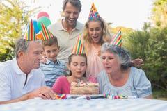 Glückliche Großfamilie, die heraus zusammen Geburtstagskerzen durchbrennt Stockbilder