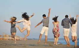Glückliche Gruppe der jungen Leute haben Spaß auf Strand Stockfotografie