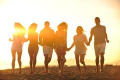 Glückliche Gruppe der jungen Leute haben Spaß auf Strand Stockbild