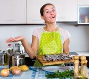 Glückliche Hausfrau, die neues Rezept versucht Stockbilder