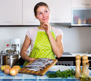 Glückliche Hausfrau, die neues Rezept versucht Stockfotografie