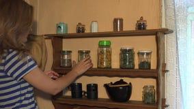 Glückliche hübsche Frau, die gesunde Kräuter für Tee im Landhausraum auswählt 4K stock footage