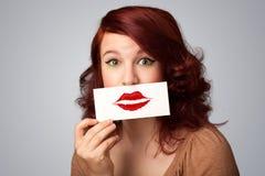 Glückliche hübsche Frau, die Karte mit Kusslippenstiftkennzeichen hält Stockfoto