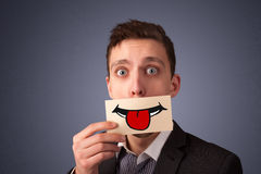 Glückliche hübsche Frau, die Karte mit lustigem smiley hält Lizenzfreie Stockfotografie