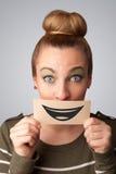 Glückliche hübsche Frau, die Karte mit lustigem smiley hält Stockfotografie