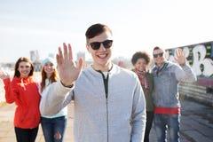 Glückliche Jugendfreunde, die Hände auf Stadtstraße wellenartig bewegen Lizenzfreie Stockbilder