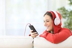 Glückliche jugendlich hörende Musik vom Telefon Lizenzfreie Stockfotografie