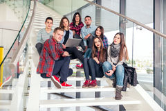 Glückliche jugendlich Mädchen und Jungen auf der Treppe Schule oder College Lizenzfreie Stockfotografie