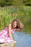 Glückliche Jugendliche, die mit Wasser spielt Stockfoto