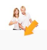 Glückliche Jugendpaare, die Daumen hoch und einen Pfeil halten Stockfotos