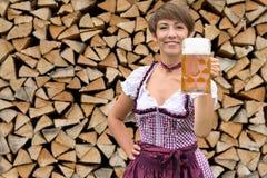 Glückliche junge bayerische Frau, die mit einem Bier röstet Lizenzfreie Stockfotografie
