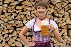 Glückliche junge bayerische Frau, die mit einem Bier röstet Stockfotos