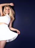 Glückliche junge Blondineaufstellung Stockfoto