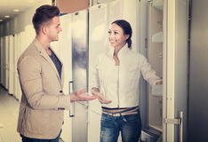 Glückliche junge Familie, die Kühlschränke im Speicher betrachtet Stockbilder