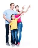 Glückliche junge Familie mit dem Kind, das oben Finger zeigt Stockfotos