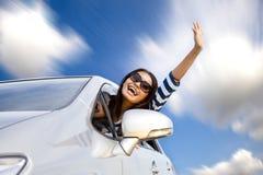 Glückliche junge Frau beim Autoantreiben Stockbild