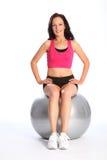 Glückliche junge Frau in der Gymnastik unter Verwendung der Übungskugel Stockfotos