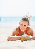 Glückliche junge Frau, die auf Strand und trinkende Kokosmilch legt Stockbild