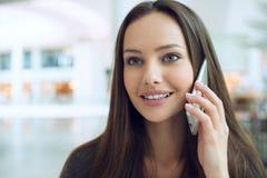 Glückliche junge Frau, die durch das Mobiltelefon Innen spricht Lizenzfreie Stockfotos