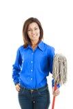 Glückliche junge Frau, die einen Besen gegen weißen Hintergrund hält Stockfoto