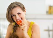 Glückliche junge Frau, die einen Biss der roten Tomate hat Stockbild