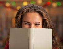Glückliche junge Frau, die hinter Buch sich versteckt Stockbild