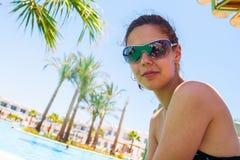 Glückliche junge Frau, die im Bikinibadeanzug über Swimmingpool und im Strand mit Palmehintergrund aufwirft Stockfotografie