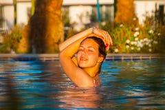 Glückliche junge Frau, die im Bikinibadeanzug über Swimmingpool und im Strand mit Palmehintergrund aufwirft Stockfotos