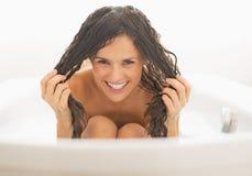 Glückliche junge Frau, die mit dem nassen Haar in der Badewanne spielt Stockfoto