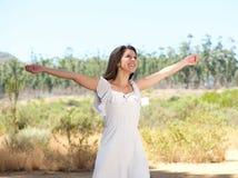 Glückliche junge Frau, die mit der Armverbreitung offen lächelt Stockfoto
