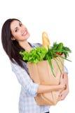 Glückliche junge Frau, die Papiertüte mit Lebensmittelgeschäften hält Stockfotos