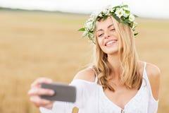 Glückliche junge Frau, die selfie durch Smartphone nimmt Lizenzfreie Stockbilder