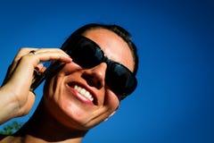 Glückliche junge Frau, die um Handy ersucht Stockfoto