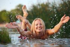 Glückliche junge Frau, die Wasser spritzt Stockbild