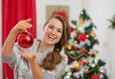 Glückliche junge Frau, die Weihnachtskugel anhält Lizenzfreie Stockfotos